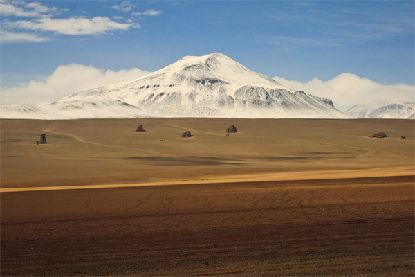 Uyuni Bolivia - Dali Desert and snow-covered mountain in the background