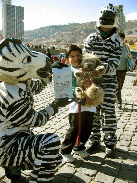 Bolivian Traffic Zebras La Paz - People dressed as zebras giving a kid holding a dog a present